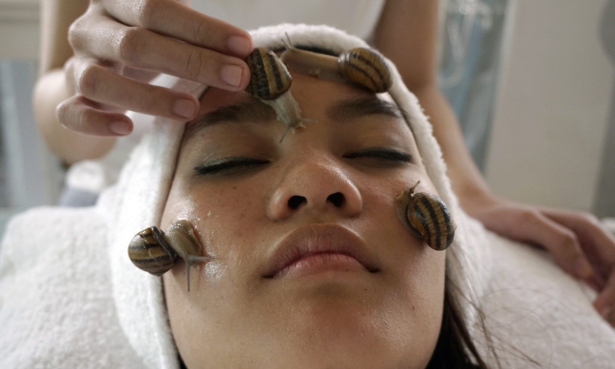 In this photo taken Monday, Jan. 19, 2015, a customer receives a beauty treatment with snails at a snail farm in Chiang Mai province, northern of Thailand. This latest addition to the global beauty and wellness craze - snail facials - should surface in the hills of the area is only natural. This Southeast Asian country ranks among the world's top spa destinations, with massage treatments of every description offered around just about every corner. (AP Photo/Denis Gray)